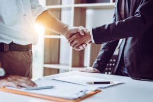 Business partners shake hands after signing a management consulting business deal. Deal papers are in the foreground.