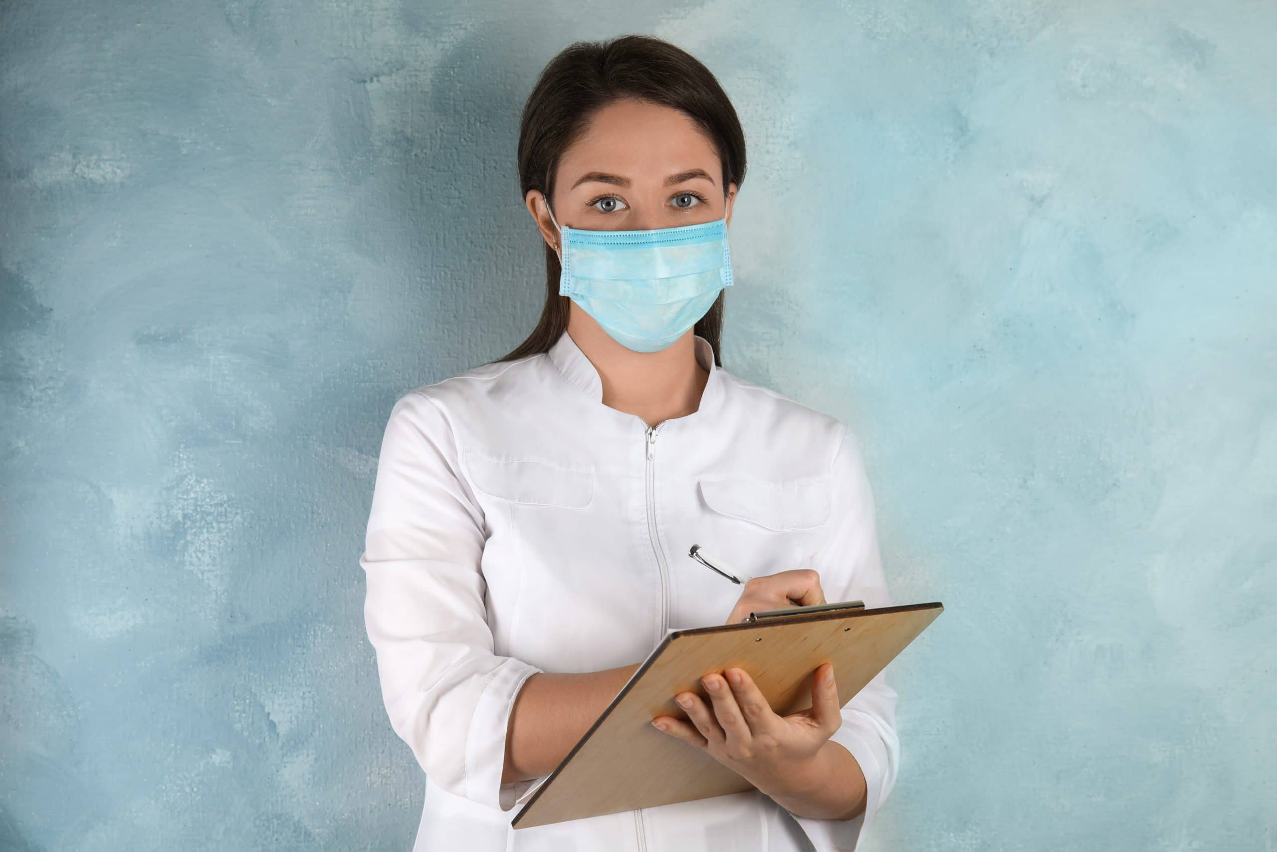 A doctor working in a long term care facility wears a disposable mask and takes notes on a clipboard.Behind her is a light blue wall.