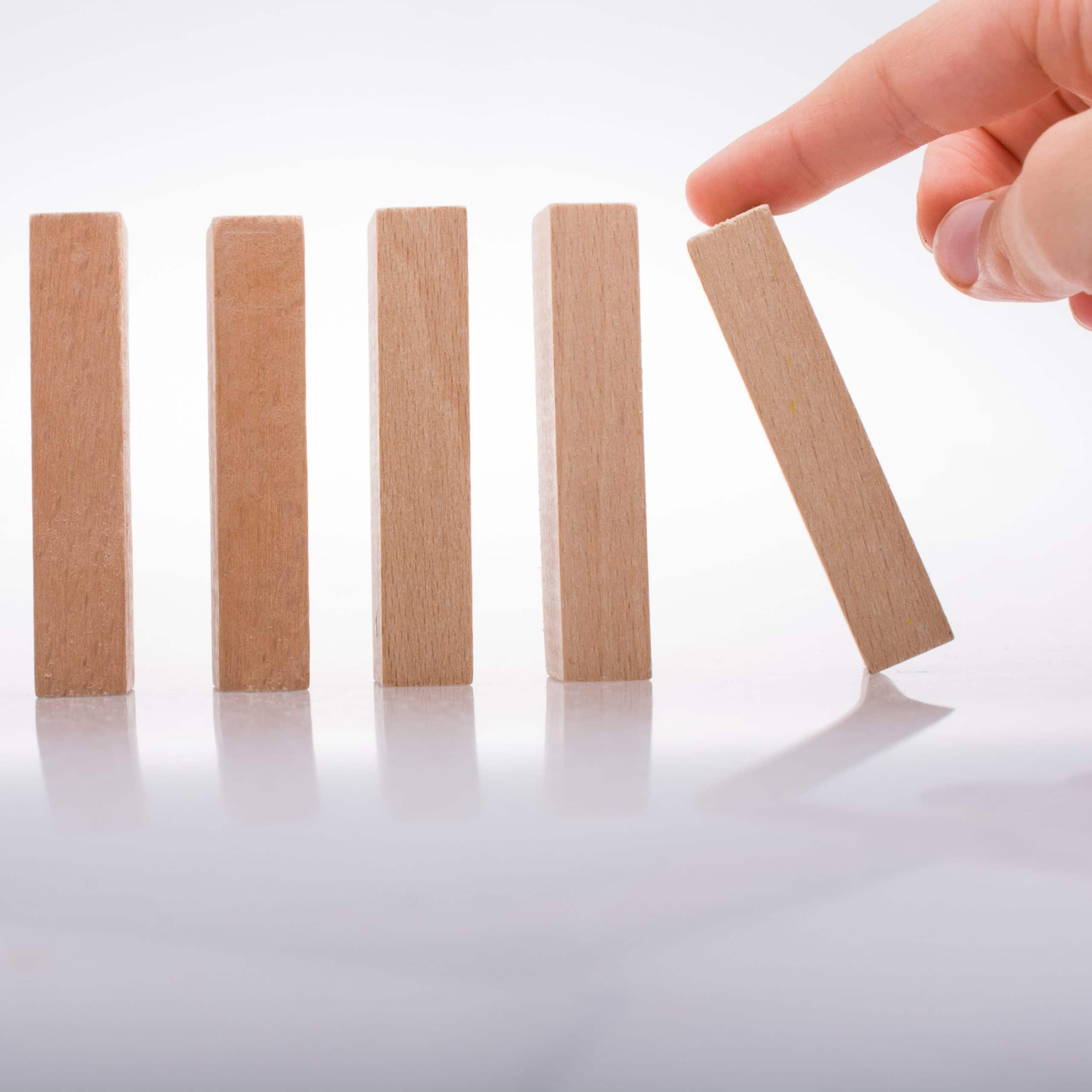 Business continuity planning represented by a hand holding wooden domino