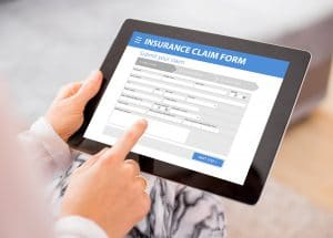 A person holds a tablet displaying an insurance claims form