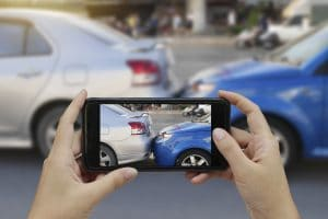 Close up of hands holding a smartphone and taking a photo at the scene of a car accident to submit as first notice of loss for a car insurance claim