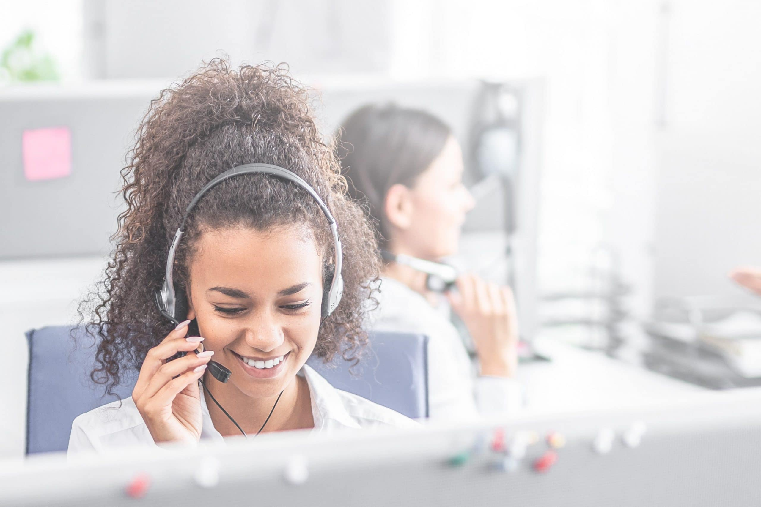 A frontline employee takes a call on a headset
