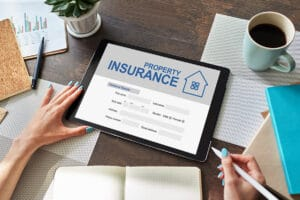 Woman completes online property insurance application on a tablet - The future of insurance distribution
