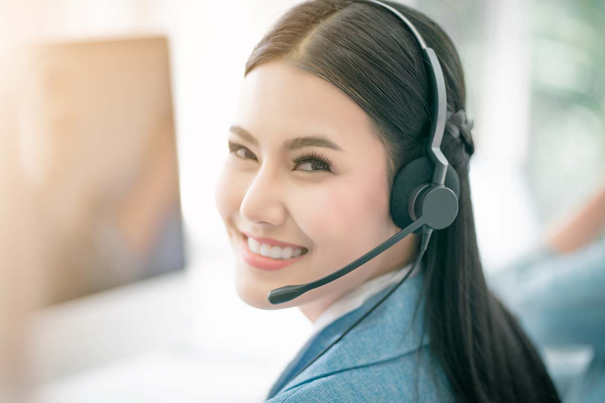 Smiling frontline employee in a contact centre wearing a headset